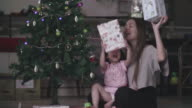 Young Mother And Baby Girl Decorating Christmas Tree With Ornaments