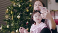 Young Mother And Baby Girl Using Smart Phone And Enjoyment In Christmas Festival