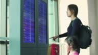 Junge Mutter und Tochter diskutieren über Plananzeige am Flughafen