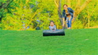 Young Mother And daughter having fun sliding down a grassy hill at Mae Moh Lampang, Thailand