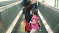 Junge Mutter und Tochter auf Laufband geht über den Flughafen