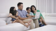 Young mother and father on computer with kids