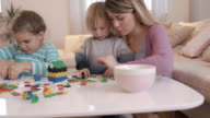 Young mother and her children playing with puzzles in the living room.