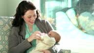 Junge Mutter Babyflasche Baby von sonnigen Fenster