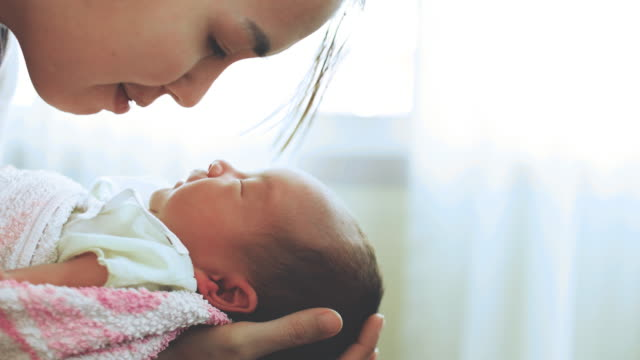 Young Mother Holding And Kissing Her Newborn Baby