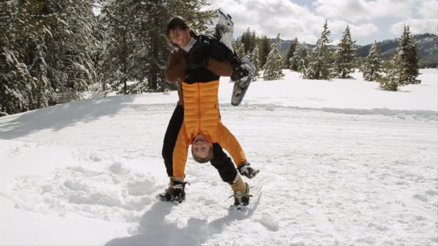 MS PAN Young mother lifting and playing with son out on winter's day / Sun Valley, Idaho, United States