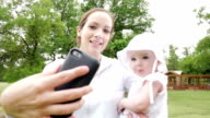Young mother taking selfie on cell phone with toddler daughter at park