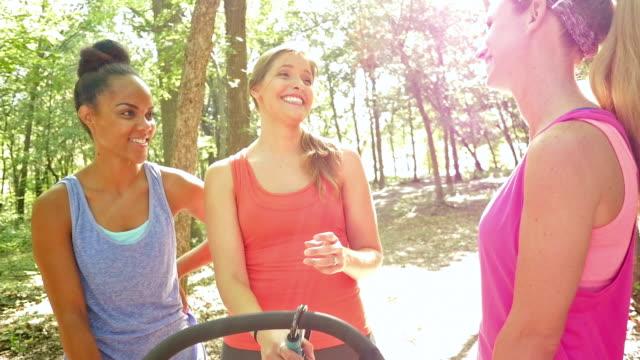 Giovani madri ridendo insieme dopo la corsa, ad esempio i passeggini