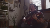 MS SLO MO. Young musician plays acoustic guitar and sings in modern apartment studio.