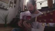 MS SLO MO. Young musician plays acoustic guitar in sunny apartment.