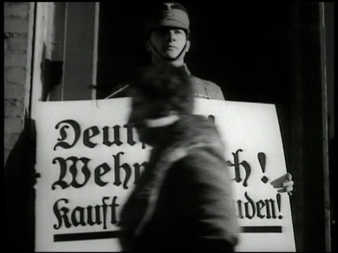 Young Nazi soldier holding sign 'Deutsche Wehrteuch kauft nicht bei juden Young adult Nazi soldiers riding in open truck locals on bicycles holding...