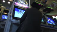 Young office worker plays video game in games arcade