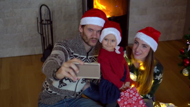 Young parents doing selfie with smart phone on Christmas's evening.