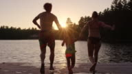 Young parents with daughter running and jumping off dock into lake