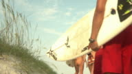 SLO MO MS LA Young people carrying surfboards running past van towards beach, Jacksonville, Florida, USA