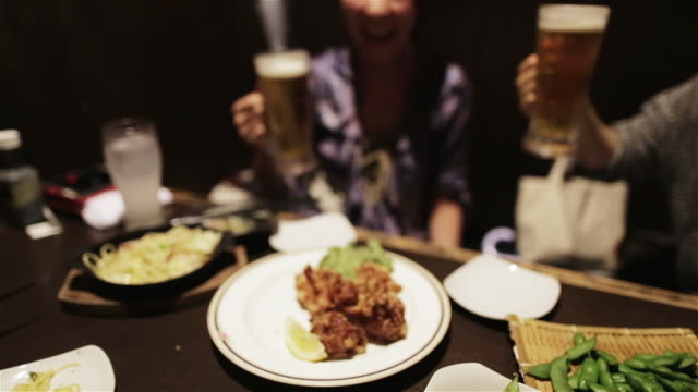 WS Young people toast with beer glasses in a Japanese pub / Tokyo, Japan