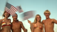 MS LA Young people waving American flags standing on beach, Jacksonville, Florida, USA
