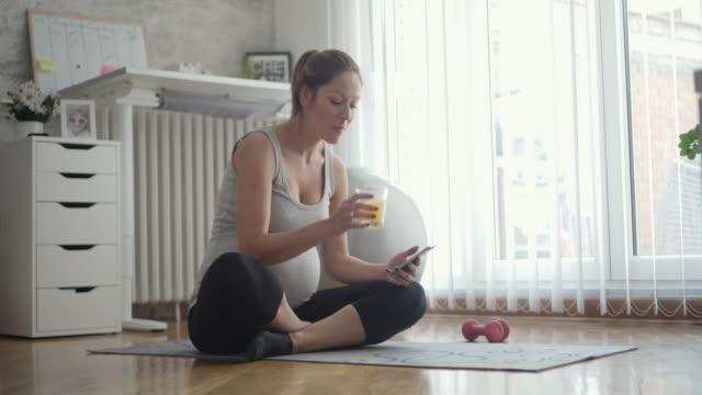 Jonge zwangere vrouw oefening en met behulp van slimme telefoon thuis.