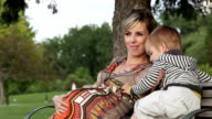 Young pregnant woman with son sitting on a bench