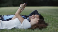 CU, LA Young, professional couple lie in grass looking up at mobile phone / Tokyo, Japan