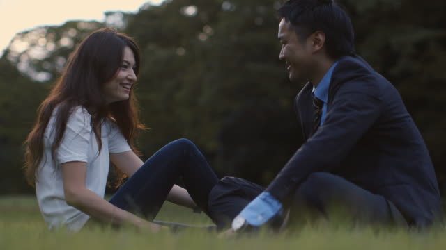 MS, LA Young, professional couple talk and laugh in the park / Tokyo, Japan