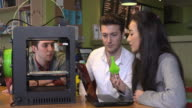 4K: Young professionals working with a 3D printer