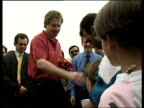 Young refugee girl presents Tony Blair with posy of wild flowers at refugee camp during Kosovan conflict Albania 18 May 99
