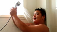 Young relaxed man taking a shower