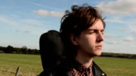 Young rock musician leaves home and walks countryside