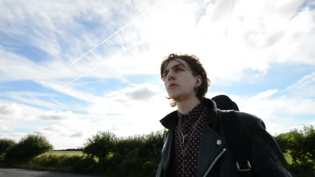 Young rock musician stands at crossroads