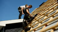 Young roofers at work on a roof of a newly built house
