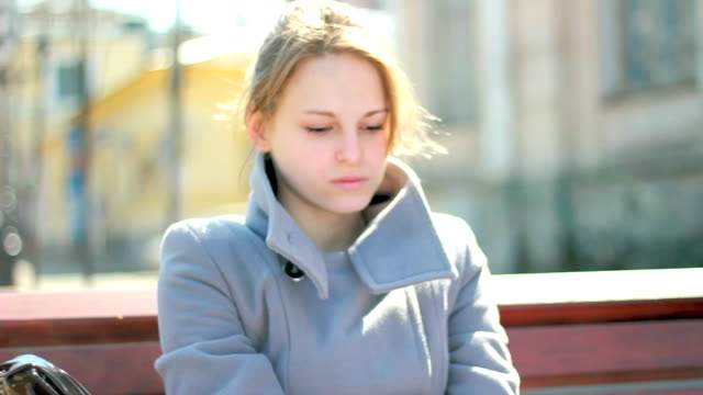 Young sad woman sitting outdoors alone, feeling emotional stress