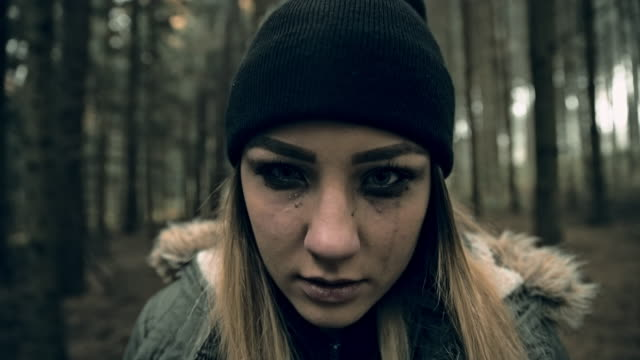 Young scary looking woman in the forest