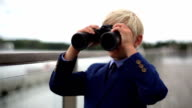 young school boy lookng through binoculars over a balustrade