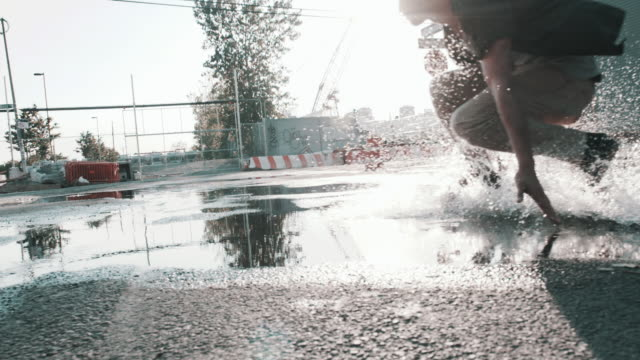 A young, skateboarder skates through a puddle in a Brooklyn street in slow motion
