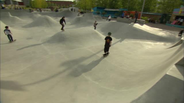 WS PAN ZI ZO TS Young skateboarders skating at large skate park, Malmo, Sweden