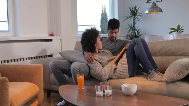 Young smiling African American couple relaxing on the sofa while reading a book and communicating.