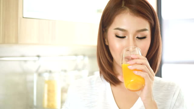 lachende mooie jongedame drinken sinaasappelsap