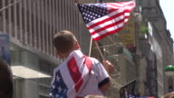 A young soccer fan waves the American Flag at the ticker tape parade in NYC celebrating the World Cup win by the US Women's Soccer Team