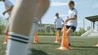 Young soccer players performing zig-zag sprint between cones