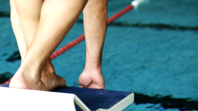 Young sportsman on a swimming starting block