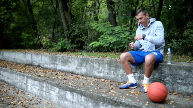 Young sportsman sitting on the stairs in the park and resting after training outdoors. Fitness, sport, lifestyle concept