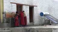 Young Student Buddhist monks of different ages doing dishes outside the school kitchen at Samstanling Monastery, Nubra Valley, Ladakh, India