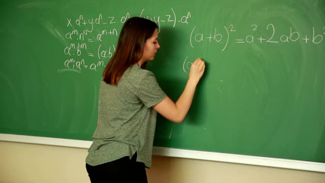 Young student writing math formula