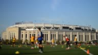 Young students play soccer with Yankee Stadium in the background in Bronx New York The silhouette of a man checks his cell phone with Yankee Stadium...