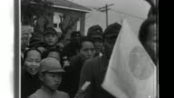 Young Taiwanese military volunteers follow Japanese soldiers in crowded streets and then participate in a formal induction ceremony conducted by...