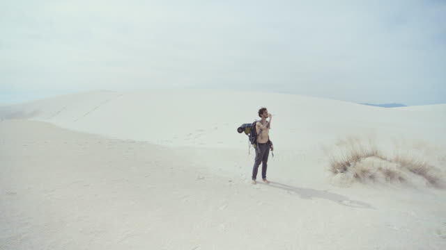 Young tattooed Caucasian man, tourist - hiker with the big backpack, drinking the bottled water in the middle of the sandy desert. White Sands National Monument, New Mexico, USA.  Aerial drone footage.