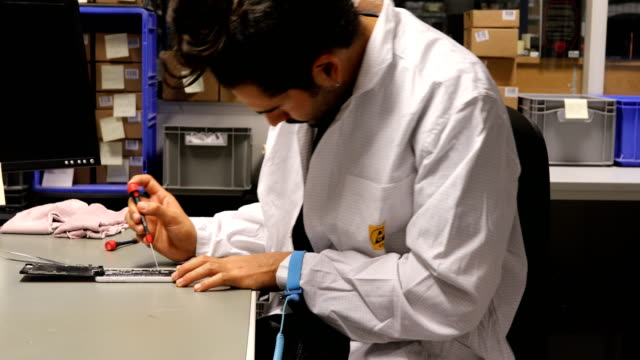Young Technician Repairing Smart Phone At Desk