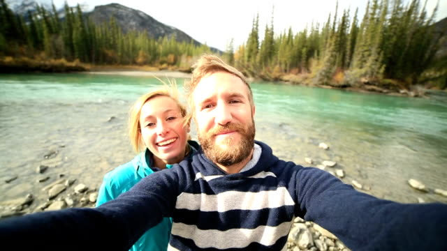 Young traveling couple by the river taking a selfie portrait