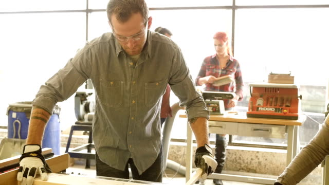 Giovane uomo alla moda Tagliere con tavolo visto in officina